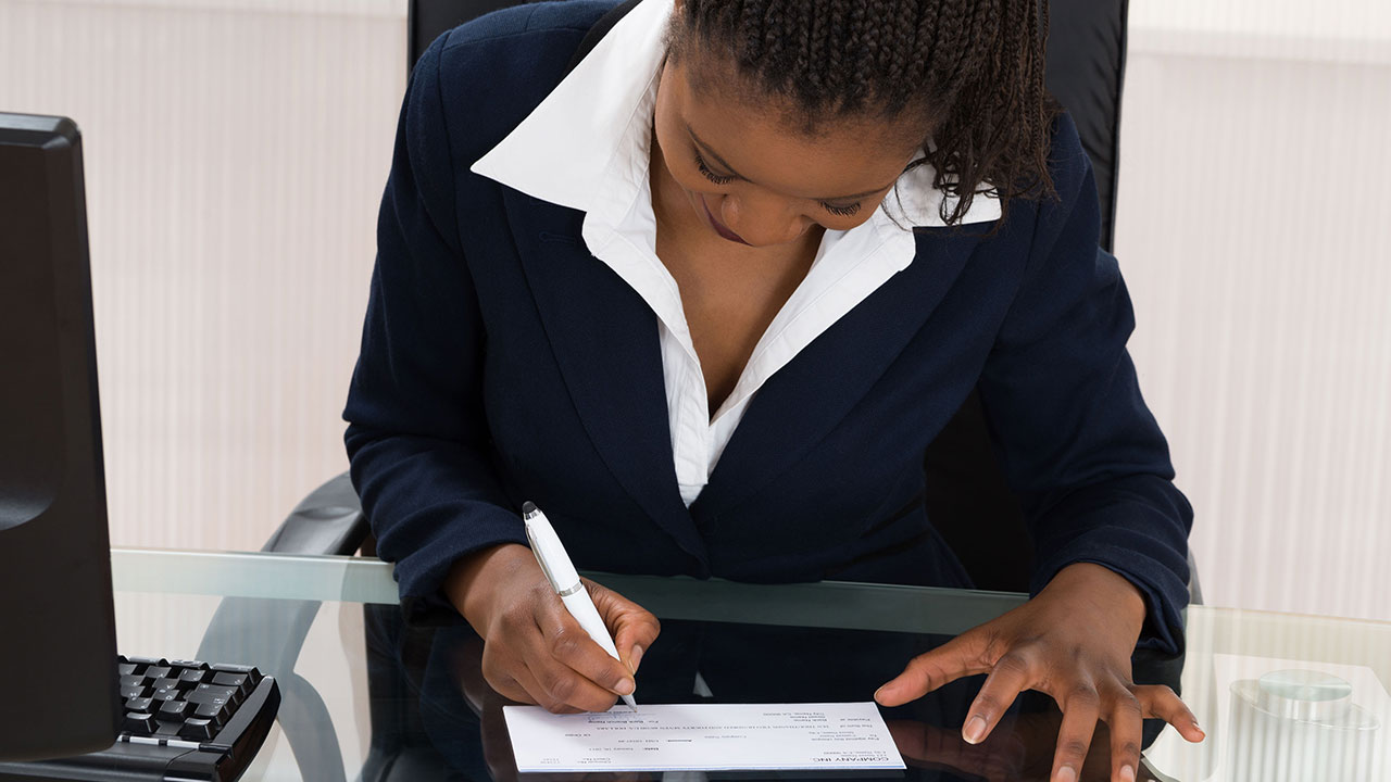 Businesswoman writing a check