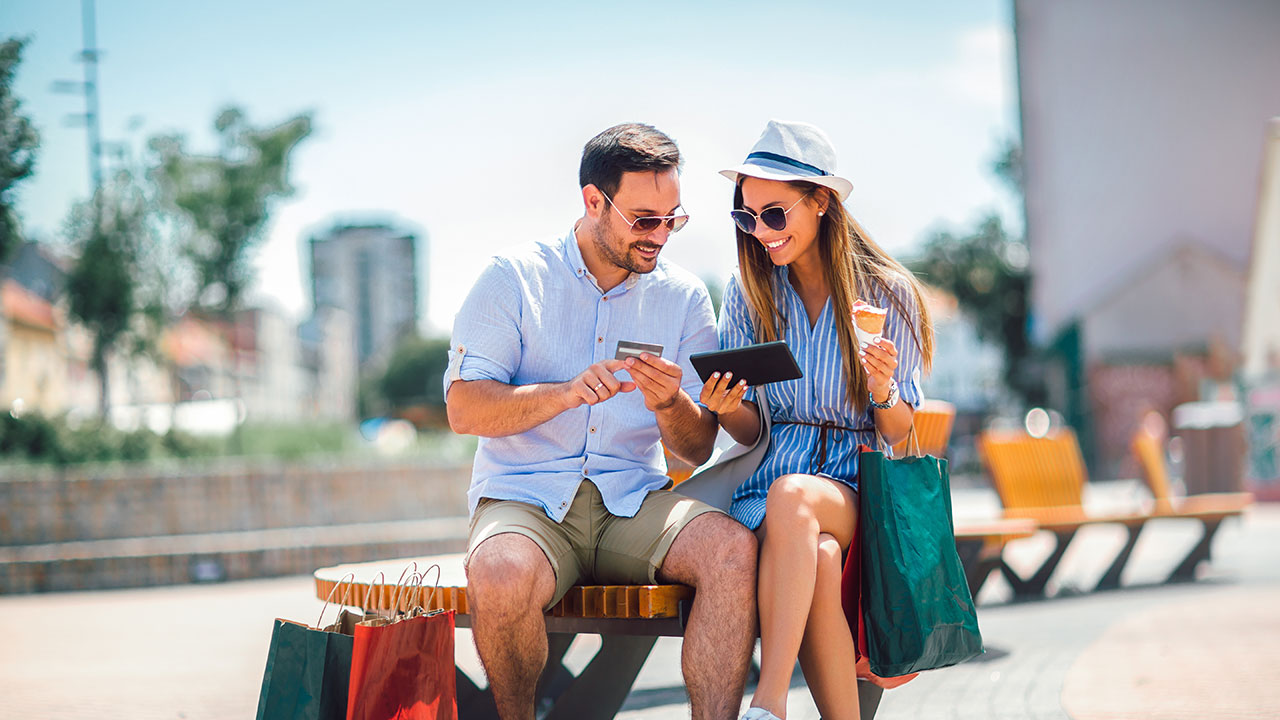 Young couple on park bench making an online purchase
