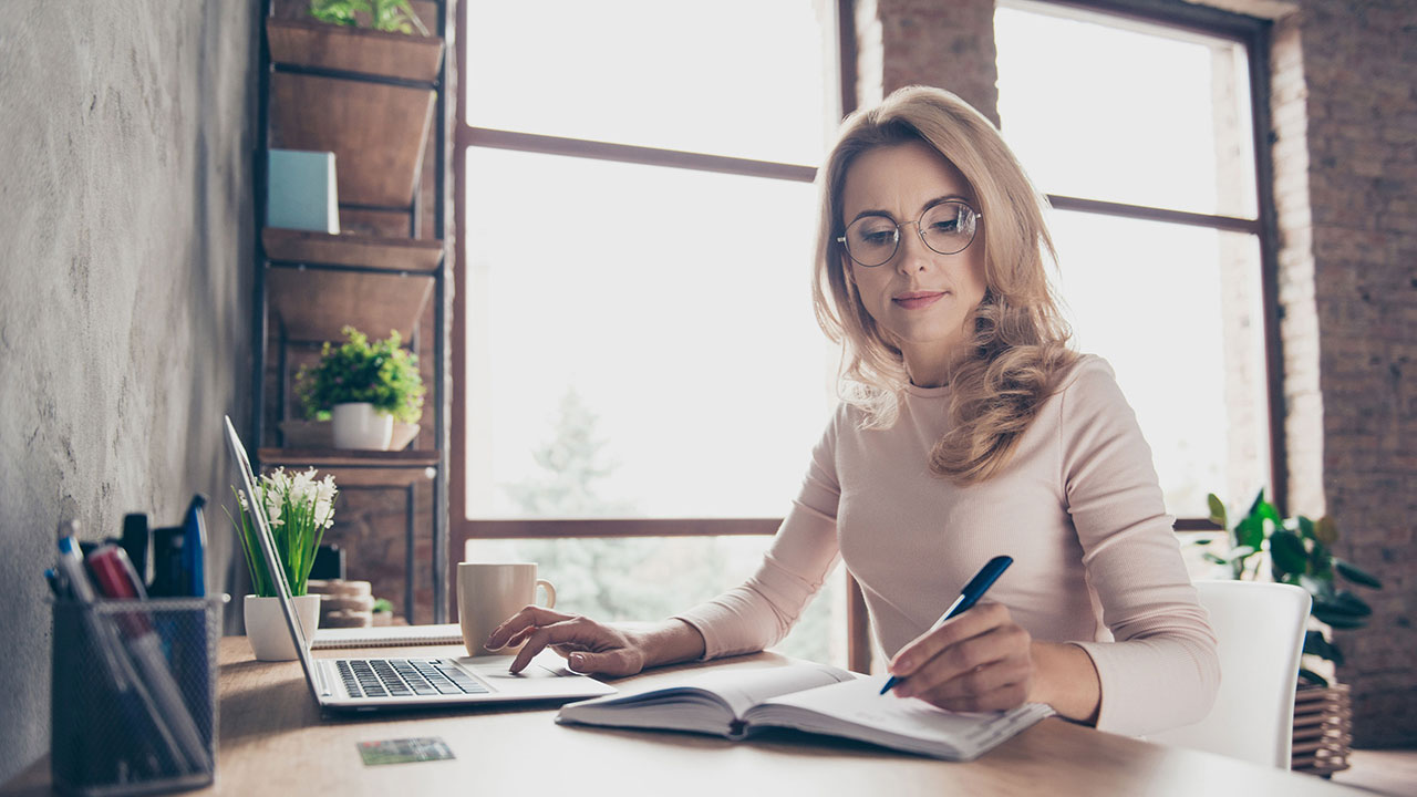 Woman at her desk working on laptop