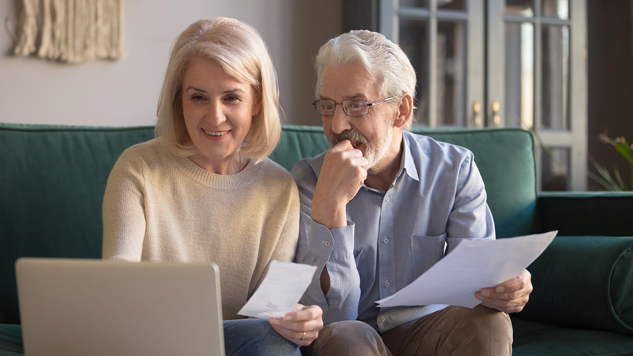 Older couple sitting on couch with laptop