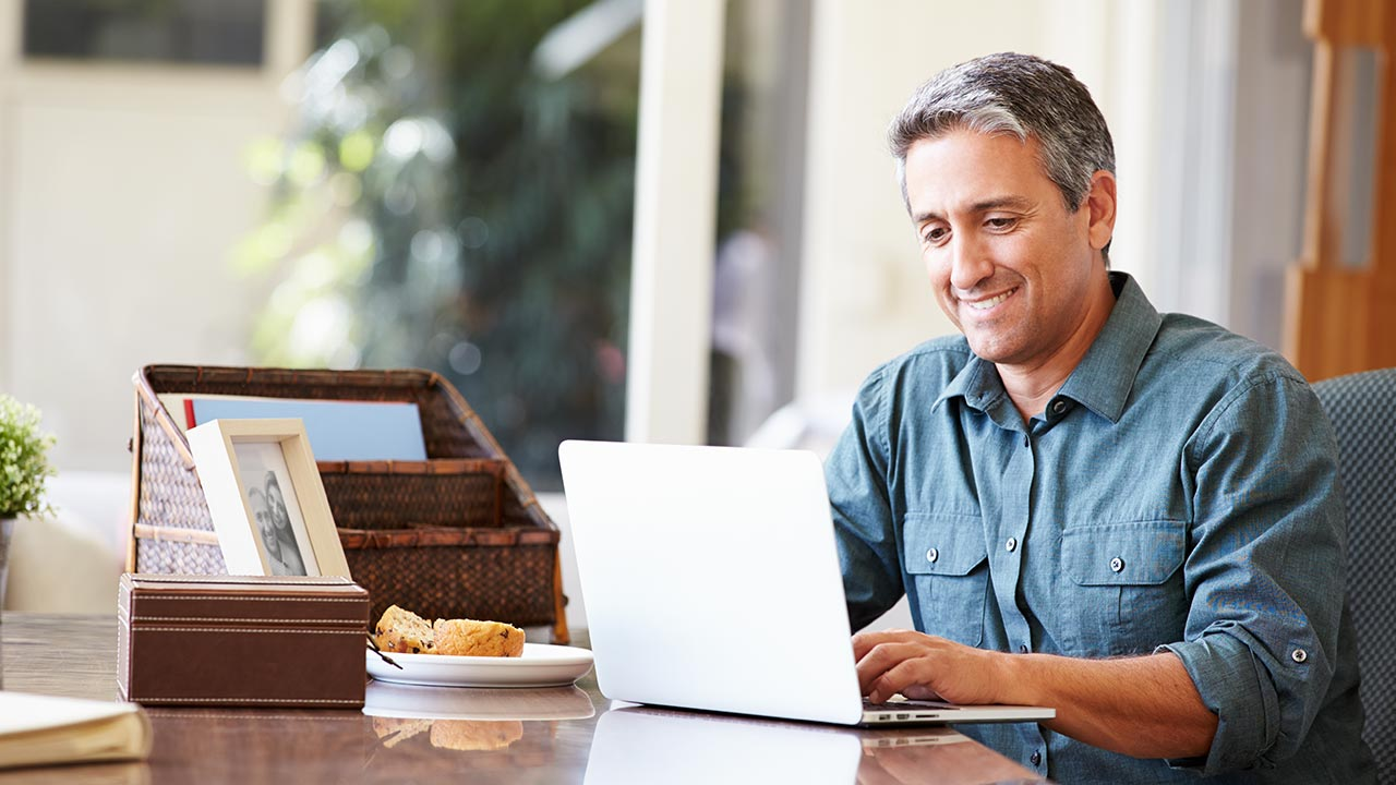 Middle-age man at kitchen table viewing laptop