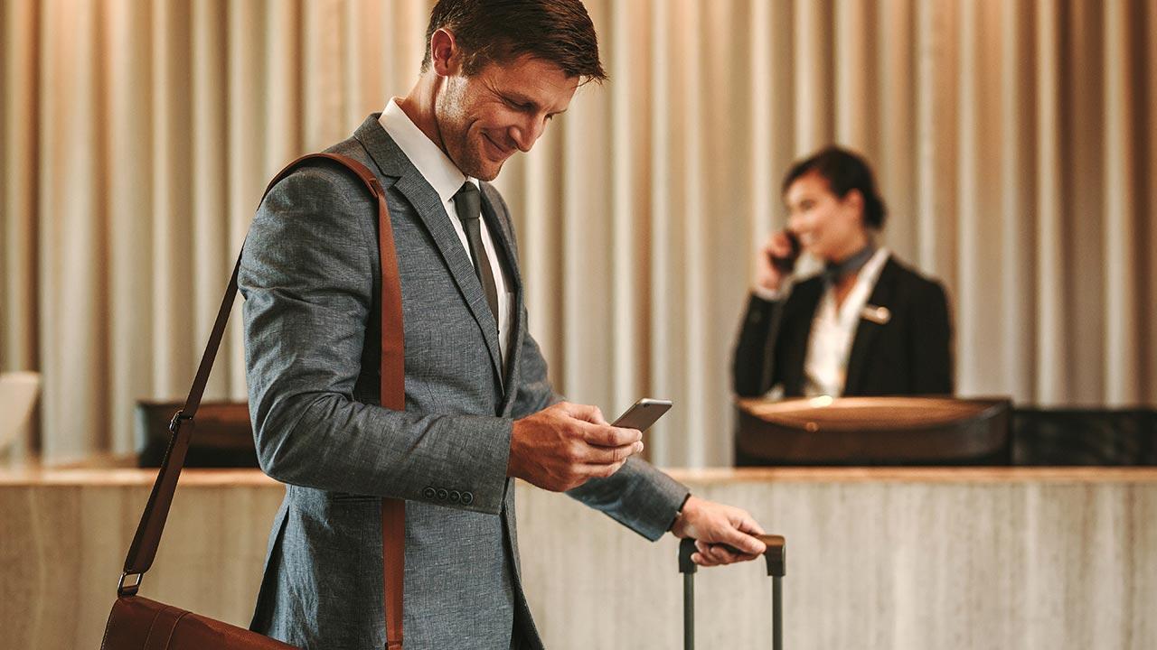 Man walking through hotel lobby looking at mobile phone.