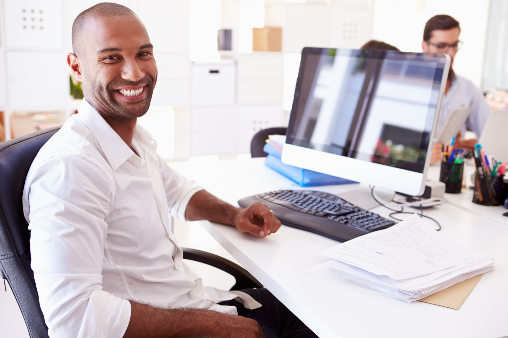 Man smiling sitting a desk.